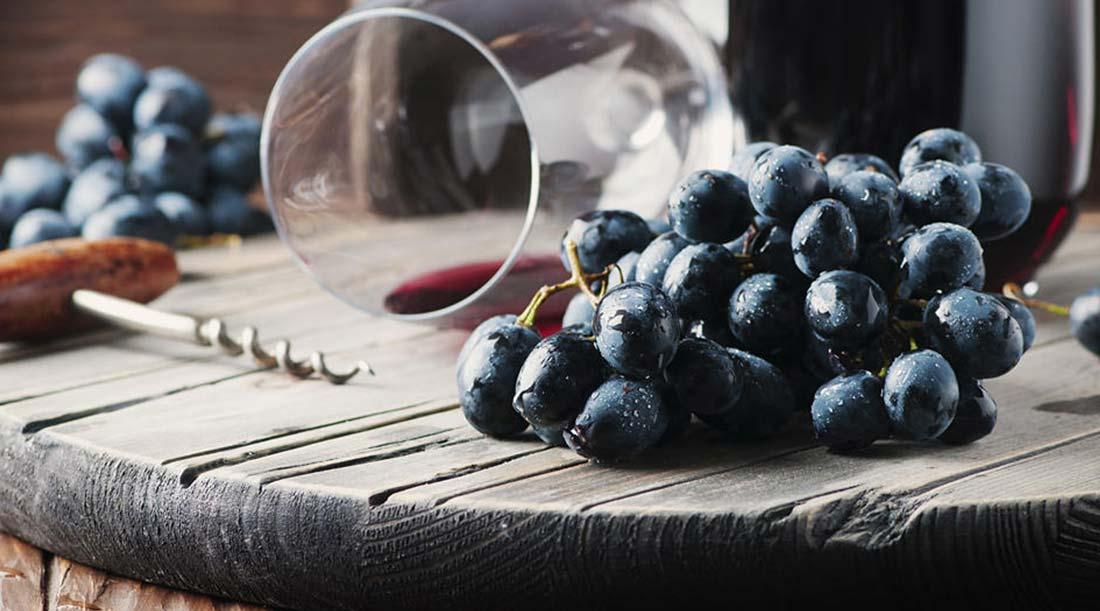 Cacho de uvas tintas e copo vinho tinto